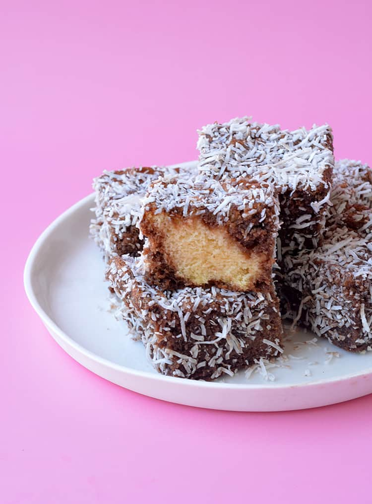 A plate of lamingtons, one with a taken out of it