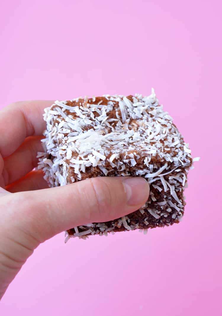 A hand holding a homemade lamington