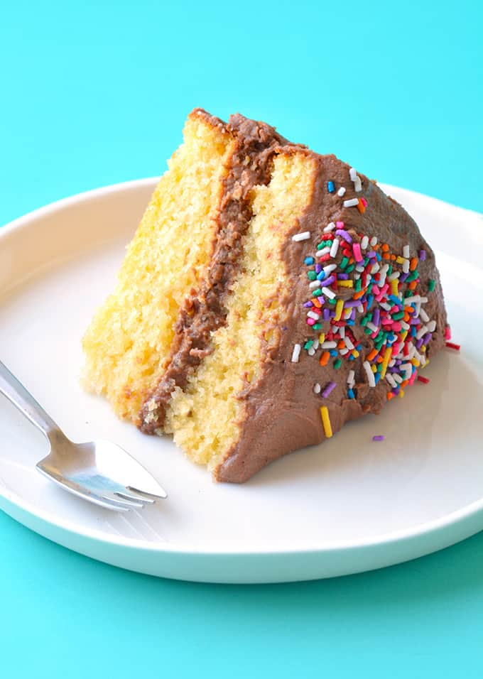A slice of Yellow Cake with Nutella frosting on a white plate