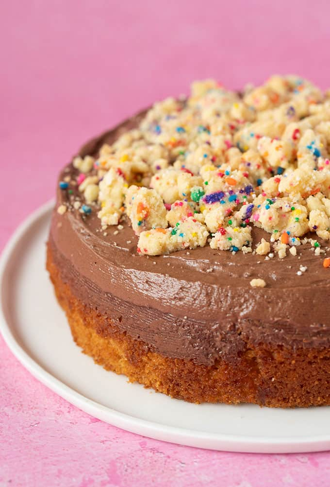 A yellow cake with chocolate frosting on a pink background