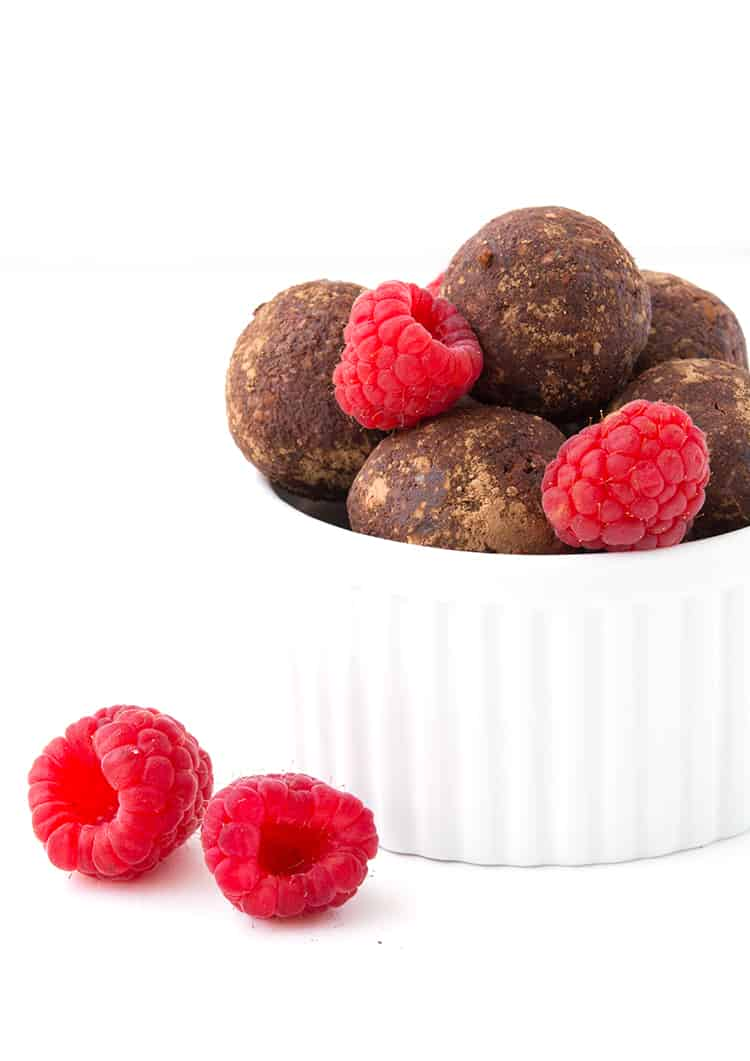 Chocolate Raspberry Bliss Balls in a white bowl with fresh raspberries