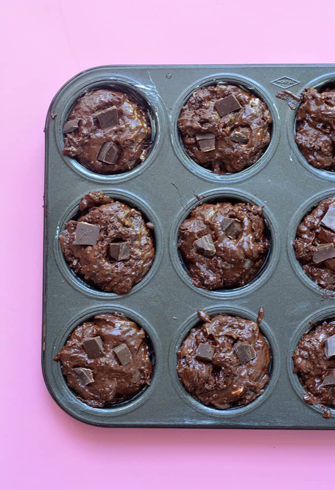 Chocolate muffin batter spooned into a muffin pan