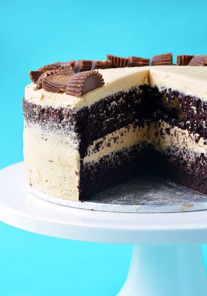 A Peanut Butter Chocolate Layer Cake with a slice taken out of it