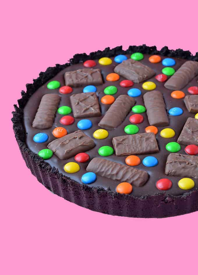 A Candy Bar Chocolate Tart on a pink background