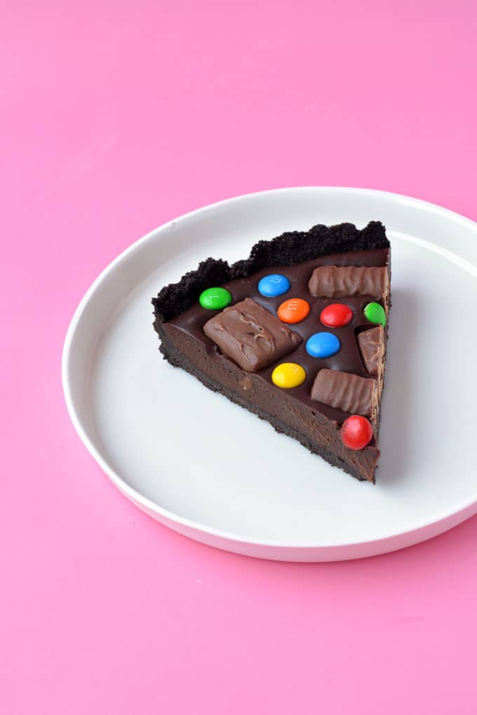 A slice of Candy Bar Chocolate Tart on a white plate