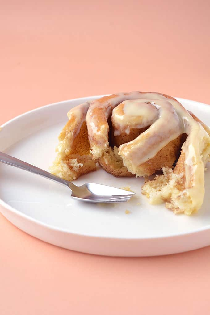 A homemade Cinnamon Roll with a bite taken out of it