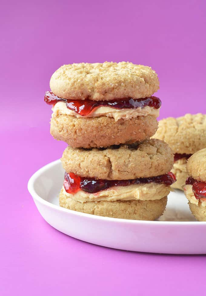 Peanut butter and jelly sandwich cookies stacked on a white plate