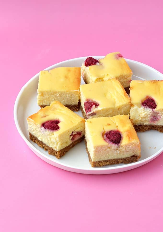 White Chocolate Raspberry Cheesecake Bars on a white plate