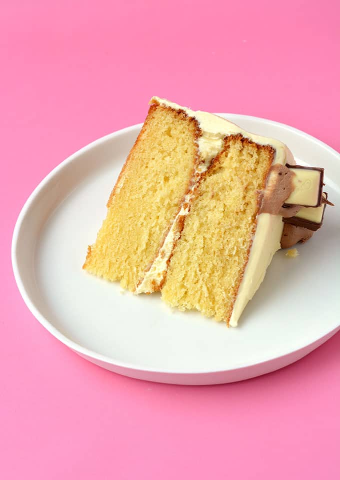 A slice of White Chocolate Layer Cake on a white plate