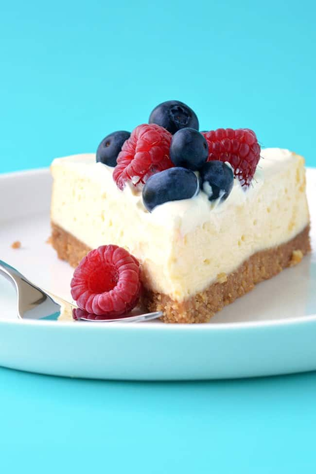 A slice of sour cream cheesecake topped with berries
