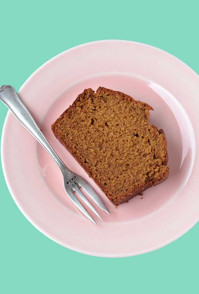Top view of a slice of Gingerbread Loaf Cake on a pink plate