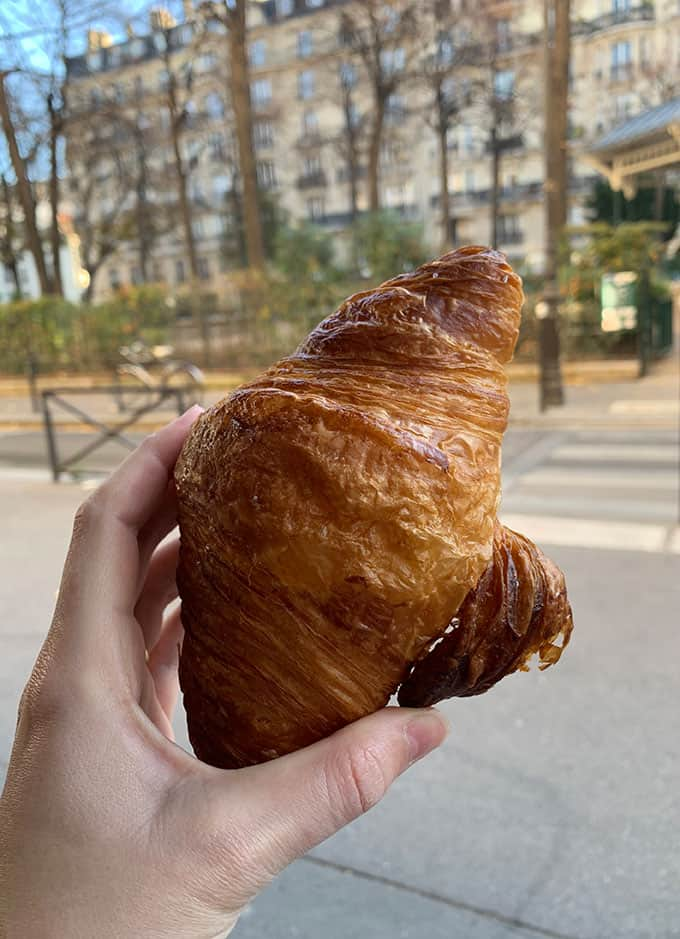 A hand holding a croissant from Ble Sucre