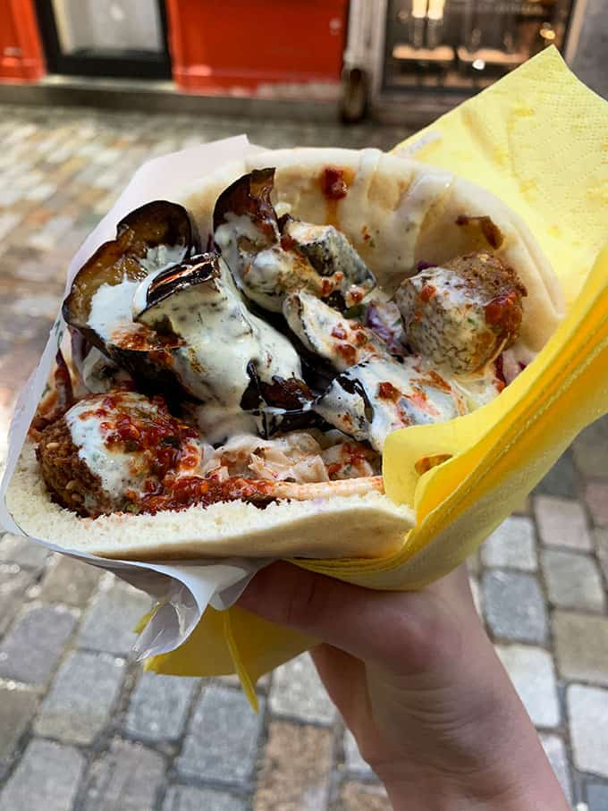A hand holding a big giant fallafel from L'As Du Fallafell in Paris