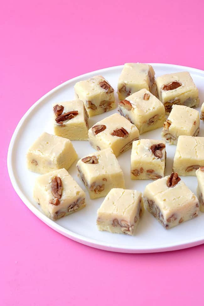 A plate of white chocolate fudge on a pink background