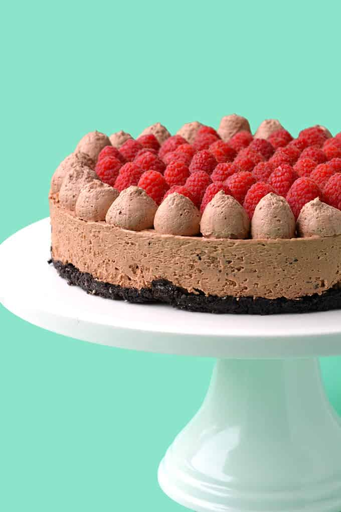 A homemade Chocolate Cheesecake on a white cake stand