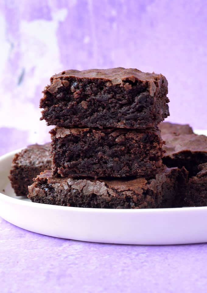 A stack of olive oil brownies on a purple background