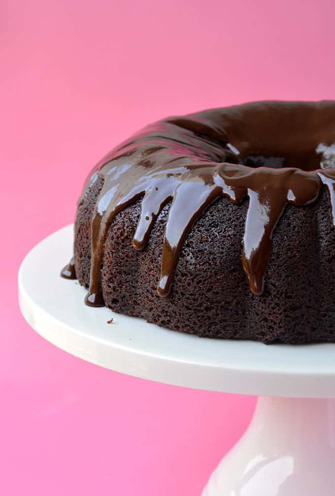 A Chocolate Sour Cream Bundt Cake sitting on a white cake stand