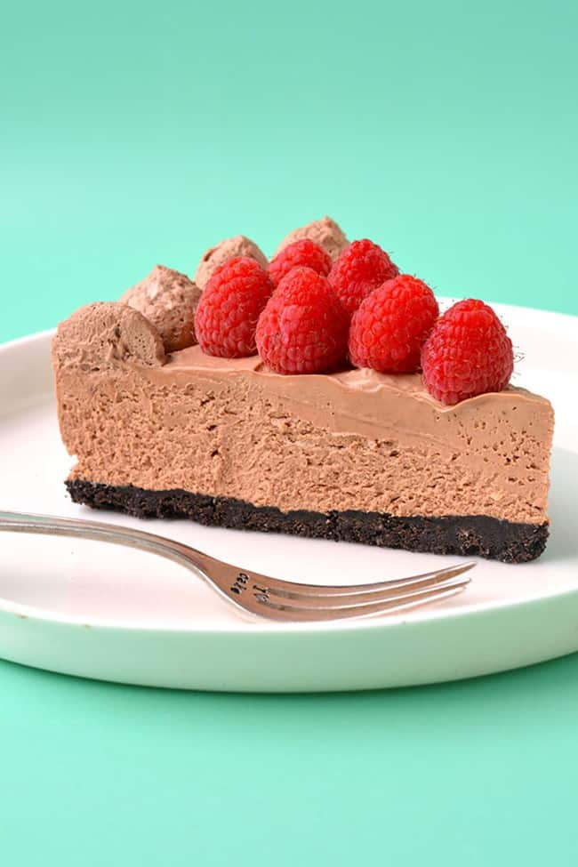 A slice of chocolate cheesecake topped with fresh raspberries