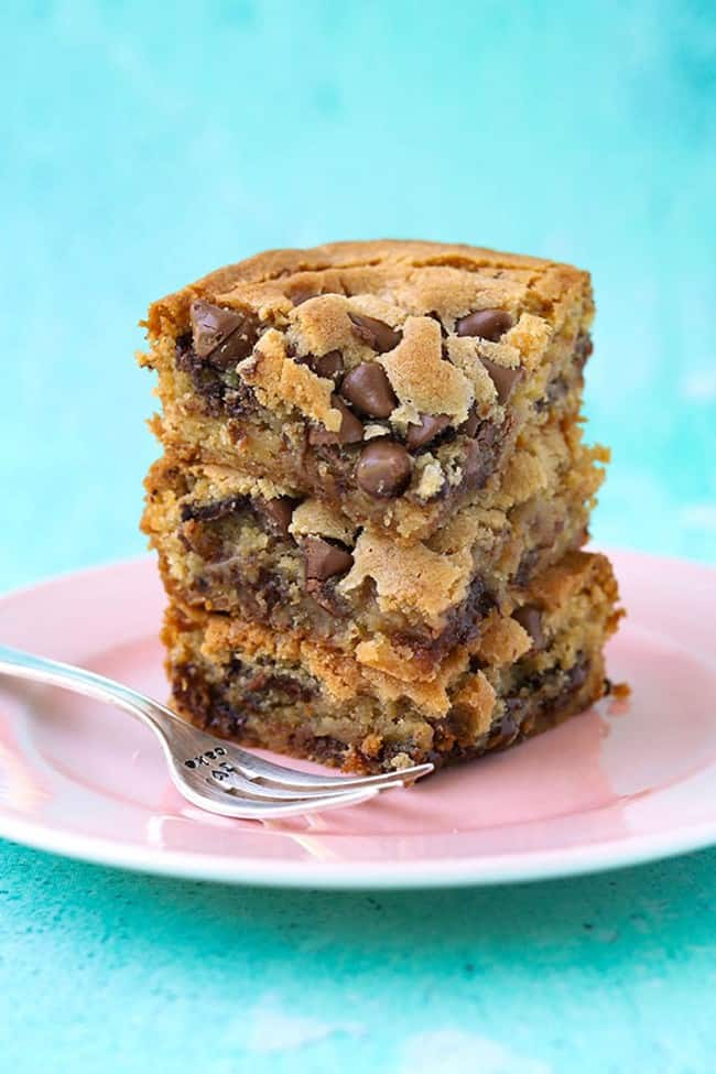 A tall stack of chocolate chip congo bars on a pink plate