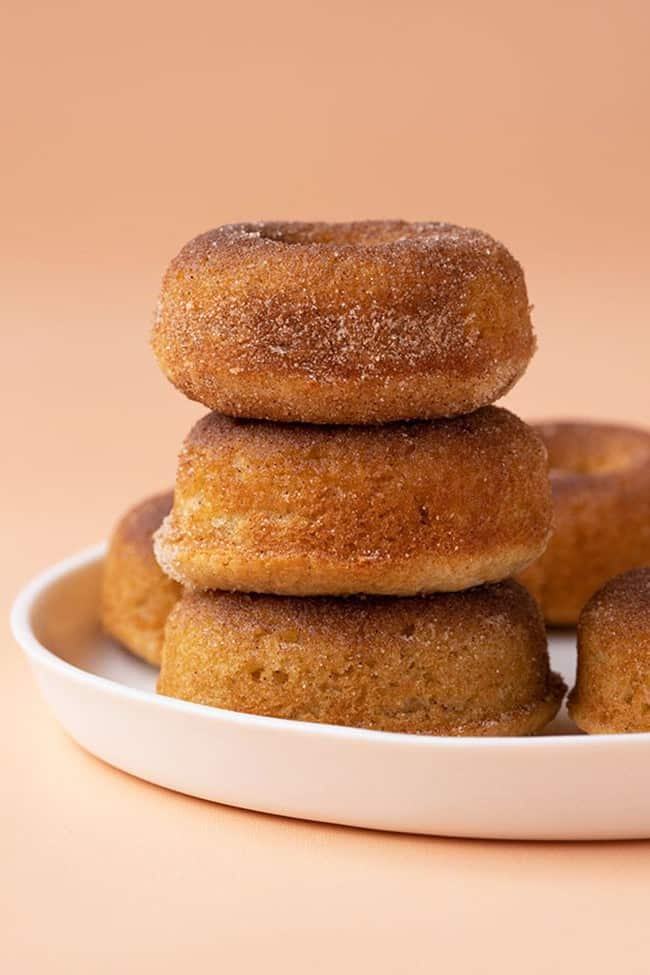 A stack of homemade cinnamon donuts on a white plate