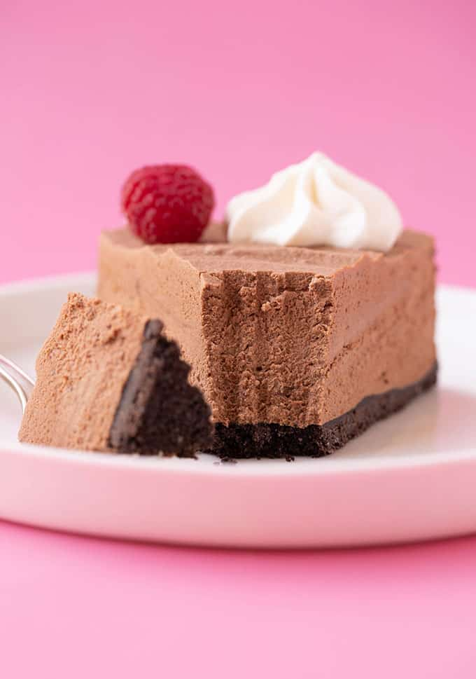 A close up of a Chocolate Mousse Cake with a bite taken out of it