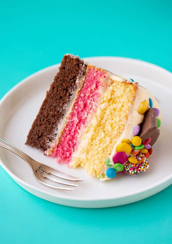 A piece of Neapolitan Cake on a white plate