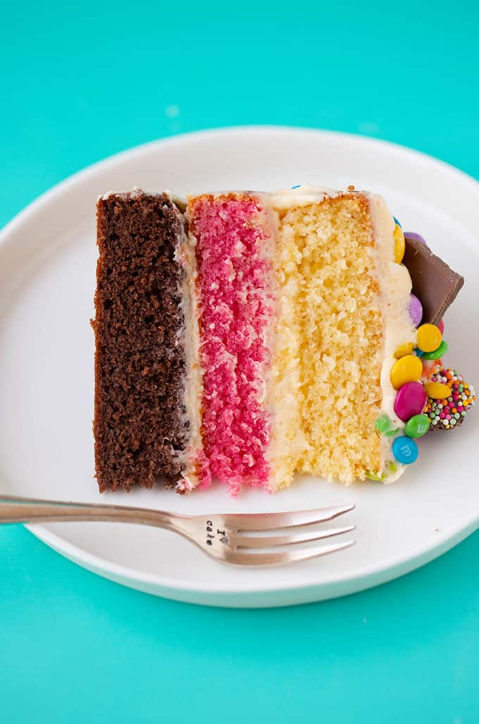 A slice of Neapolitan Cake on a white plate