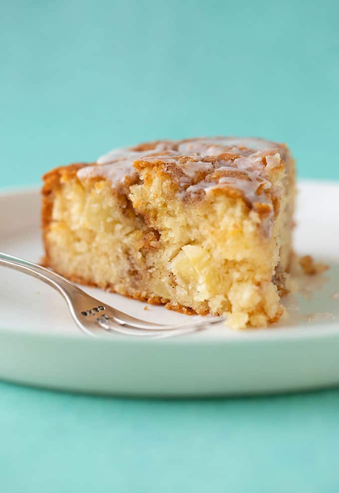 Close up of a slice of apple cake on a green background