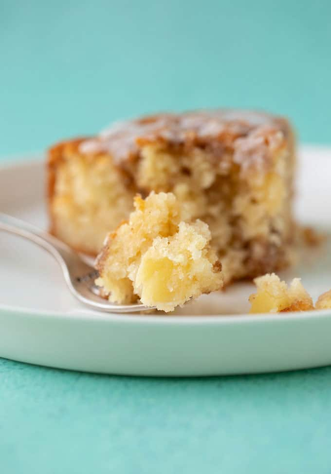 A slice of Cinnamon Apple Cake with a fork