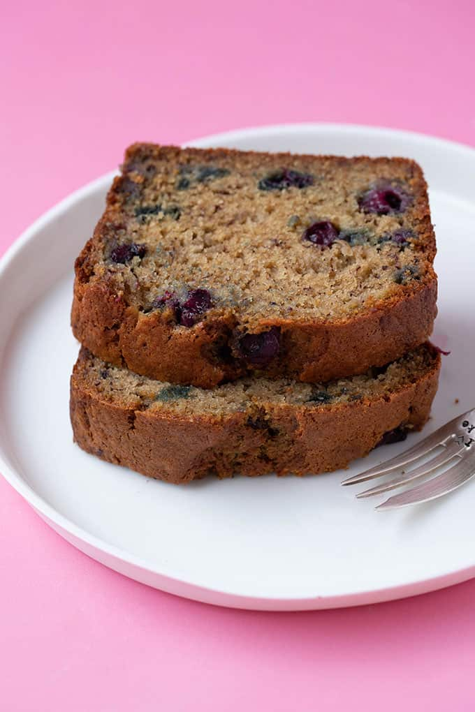 Two slices of blueberry banana bread of a white plate