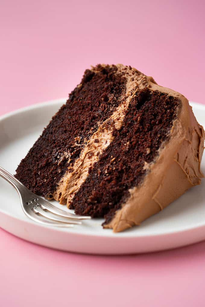 A big slice of Chocolate Fudge Cake on a white plate