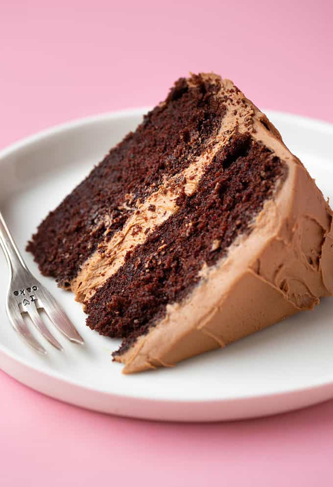 A piece of two layer chocolate cake on a white plate