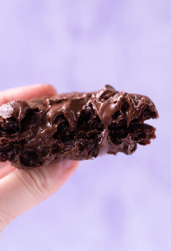 A hand holding gooey chocolate cookies