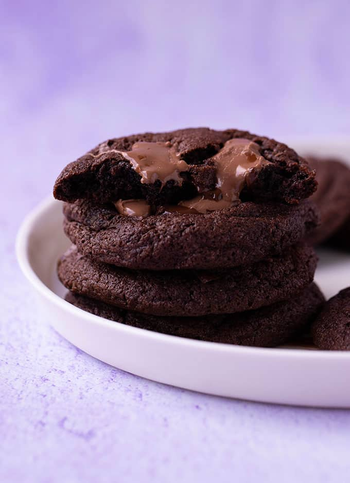 A stack of homemade Chocolate Fudge Cookies on a white plate