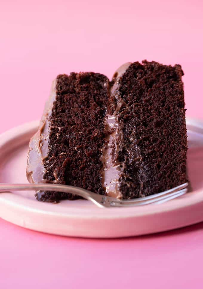 A big piece of chocolate cake on a pink plate