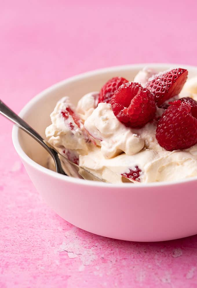 A bowl of eton mess on a pink background