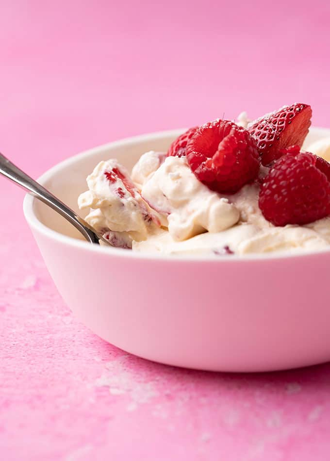 A bowl of Eton Mess topped with raspberries and strawberries