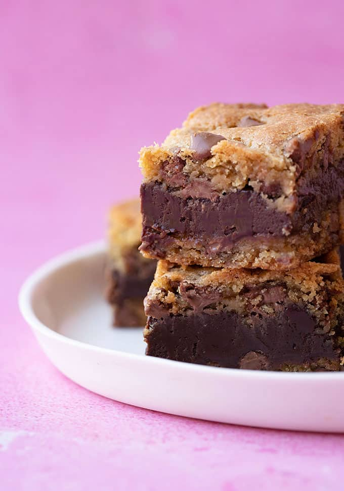 A stack of homemade Fudge Stuffed Cookie Bars on a white plate