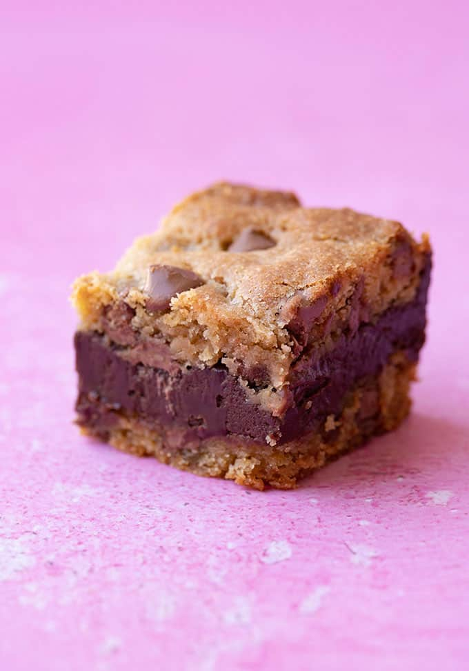 A close up of a Fudge Stuffed Cookie Bar on a pink background
