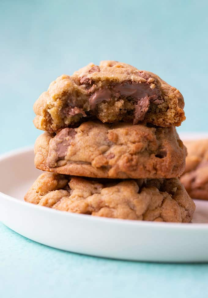 A stack of chocolate chip chocolate cookies on a white plate
