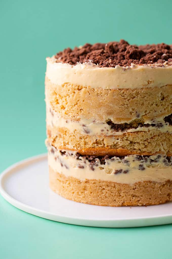 A three layer peanut butter cake on a green background