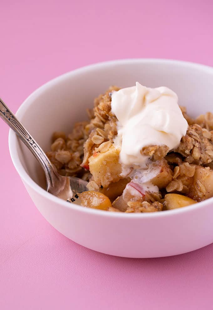 A bowl of Apple Cruumble topped with whipped cream on a pink background.