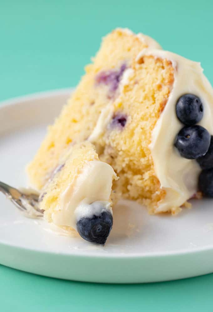 A slice of homemade Lemon Blueberry Cake with a bite taken out of it