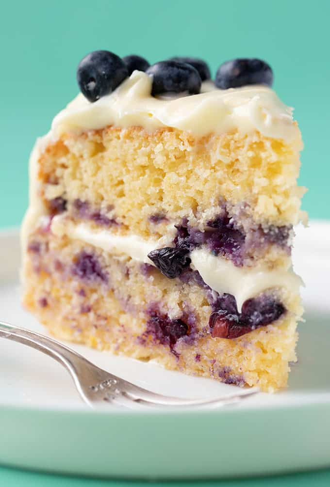 A big slice of Lemon Blueberry Cake with cream cheese frosting