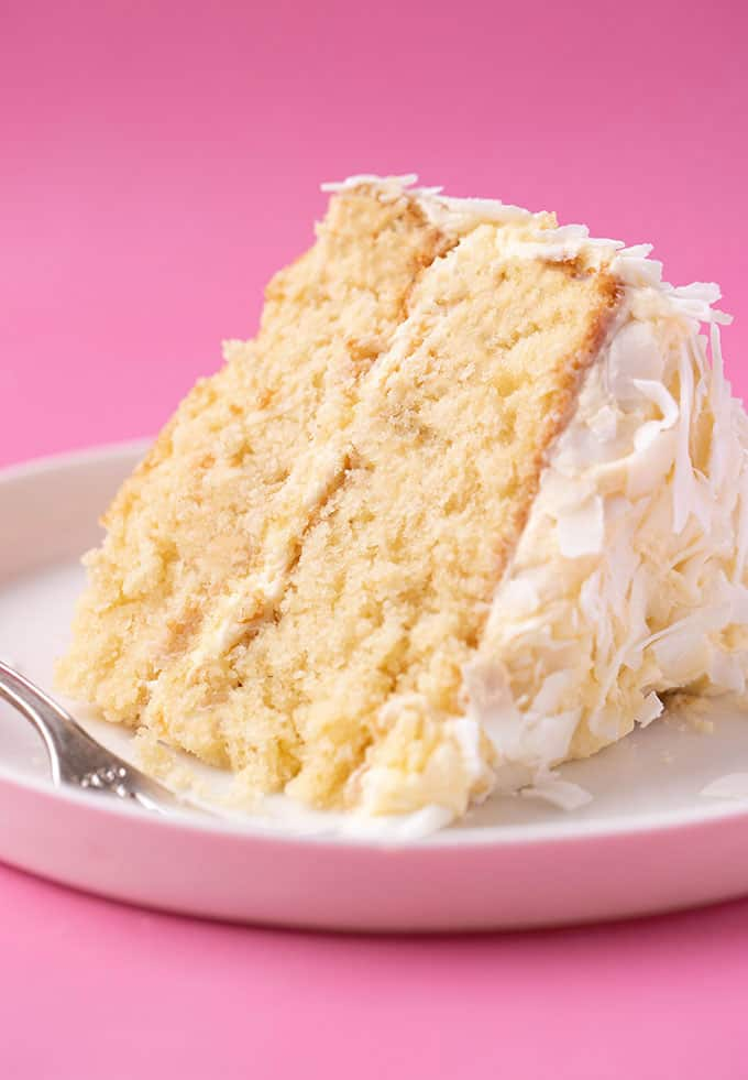 A big slice of Coconut Cake on a plate with a fork