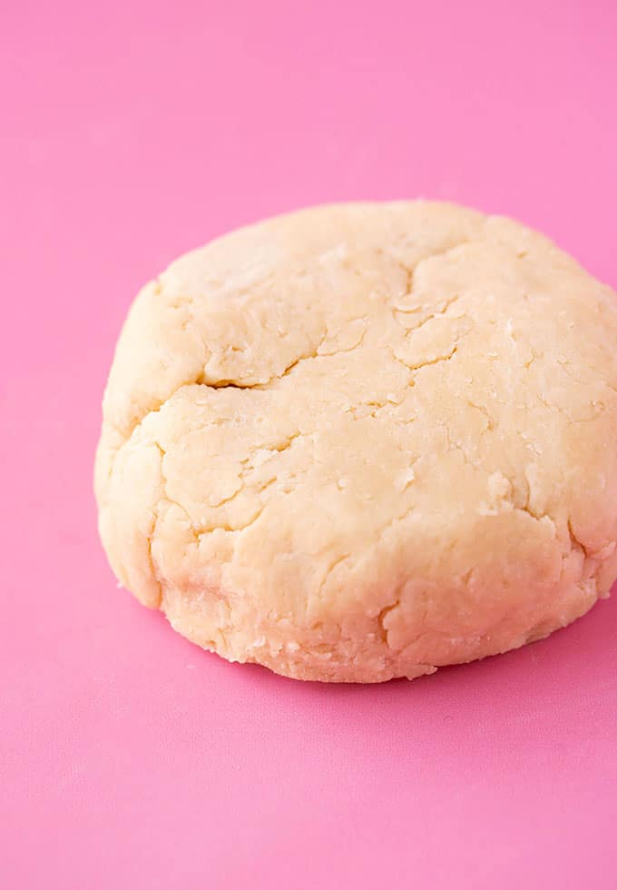 A ball of shortcrust dough on a pink background
