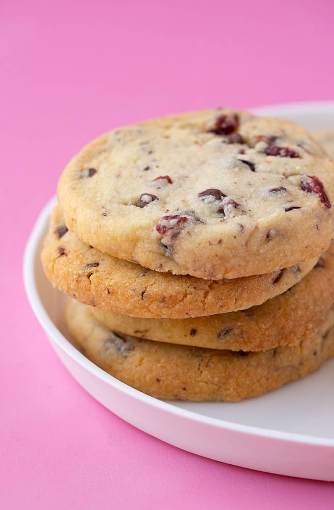 A stack of Chocolate Cranberry Shortbread Cookies on a white plate