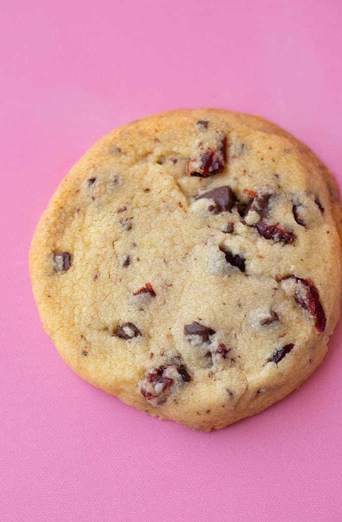 A Chocolate Cranberry Shortbread Cookie on a pink background