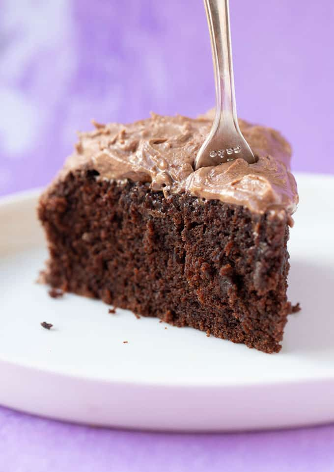 A slice of gluten free chocolate cake with a fork stuck in it
