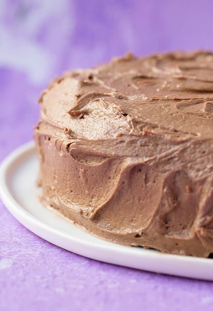 Close up of a gluten free chocolate cake covered in frosting